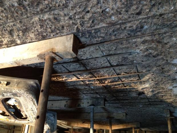 Udstrakte betonsprængninger med synlig armering og nødunderstøtning